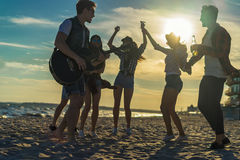 Happy friends dancing on the beach. Men is playing guitar Stock Photos