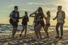 Happy friends dancing on the beach. Men is playing guitar. And singing songs. Party on sand. Golden sunset time royalty free stock photo