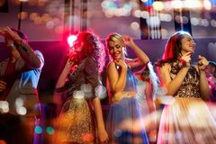 Happy friends dancing in club with holidays lights. Party, holidays, celebration, nightlife and people concept - happy friends dancing in club with holidays Royalty Free Stock Images