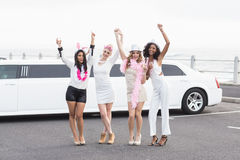 Happy friends dancing in front of a limousine Royalty Free Stock Photography