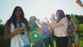 Happy friends dancing, having fun outdoors. Happy friends dancing, having fun and enjoying party outdoors in sunny summer day. Girls are holding champagne stock footage