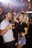 Happy friends dancing while holding beer mugs at nightclub Royalty Free Stock Image