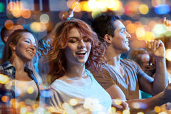 Happy friends dancing at night club Stock Photography