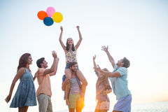 Happy friends dancing on the sand with balloon Stock Photos