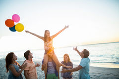 Happy friends dancing on the sand with balloon Royalty Free Stock Images