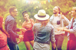 Happy friends dancing at summer party in garden Stock Photo