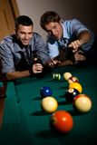 Happy friends discussing game of billiard at table Stock Photo