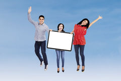 Happy friends displaying blank board Royalty Free Stock Photos