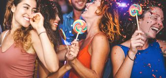 Happy friends doing party dancing in the nightclub - Trendy young people having fun celebrating together with confetti and candy. Lollipops in disco stock photo