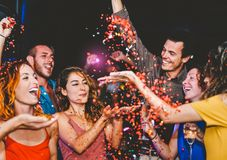 Happy friends doing party throwing confetti in the club - Millennial young people having fun celebrating in the nightclub