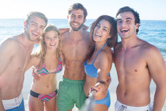 Happy friends doing pictures with selfie stick. At the beach Royalty Free Stock Images