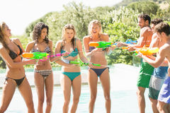 Happy friends doing water gun battle Stock Photography