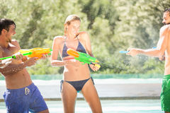 Happy friends doing water gun battle Stock Photos