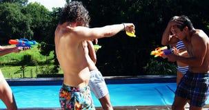 Happy friends doing water gun battle stock video footage