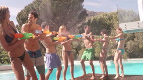 Happy friends doing water gun battle. Nearby swimming pool stock video