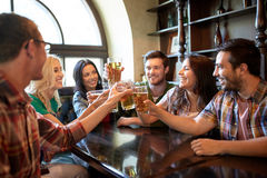 Happy friends drinking beer at bar or pub. People, leisure, friendship and celebration concept - happy friends drinking draft beer and clinking glasses at bar or Royalty Free Stock Photo