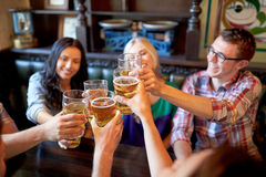Happy friends drinking beer at bar or pub. People, leisure, friendship and celebration concept - happy friends drinking draft beer and clinking glasses at bar or royalty free stock photos