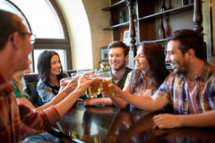 Happy friends drinking beer at bar or pub. People, leisure, friendship and celebration concept - happy friends drinking draft beer and clinking glasses at bar or Stock Image
