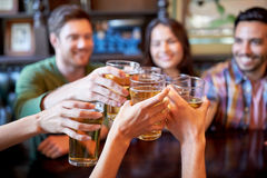 Happy friends drinking beer at bar or pub. People, leisure, friendship and celebration concept - happy friends drinking draft beer and clinking glasses at bar or Stock Images