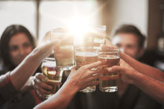 Happy friends drinking beer at bar or pub. People, leisure, friendship and celebration concept - happy friends drinking draft beer and clinking glasses at bar or royalty free stock photography