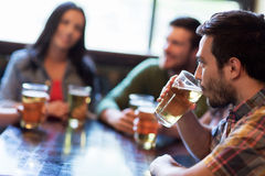 Happy friends drinking beer at bar or pub. People, leisure, friendship and communication concept - happy friends drinking beer and talking at bar or pub Royalty Free Stock Images