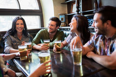 Happy friends drinking beer at bar or pub. People, leisure, friendship and communication concept - happy friends drinking beer, talking and clinking glasses at Royalty Free Stock Image