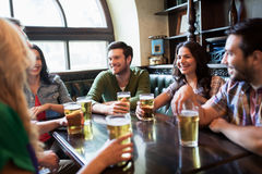 Happy friends drinking beer at bar or pub. People, leisure, friendship and communication concept - happy friends drinking beer, talking and clinking glasses at Stock Image