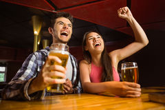 Happy friends drinking beer and cheering together Royalty Free Stock Images