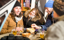 Happy friends drinking beer and eating chips at ski resort chalet Stock Images