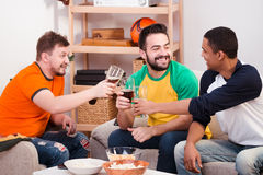 Happy friends drinking beer at home Royalty Free Stock Images