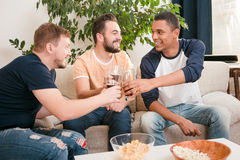 Happy friends drinking beer at home. Picture of happy friends drinking alcohol drinks at home all together. Handsome men drinking beers and eating pop corn Royalty Free Stock Images