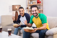 Happy friends drinking beer at home. Picture of fappy friends drinking beer and eating pop corn at home while watching football on TV. Happy handsome men posing Stock Images