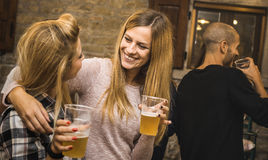 Happy friends drinking beer at house party - Friendship concept. With fancy people having fun together - Young women sharing joy moment celebrating at home Stock Photos