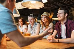 Happy friends drinking beer and talking at bar. People, leisure, friendship and communication concept - group of happy smiling friends drinking beer and talking Stock Photo