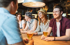 Happy friends drinking beer and talking at bar. People, leisure, friendship and communication concept - group of happy smiling friends drinking beer and talking Royalty Free Stock Photo