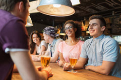 Happy friends drinking beer and talking at bar. People, leisure, friendship and communication concept - group of happy smiling friends drinking beer and talking Royalty Free Stock Images