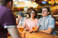 Happy friends drinking beer and talking at bar Royalty Free Stock Photography