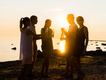 Happy friends drinking drinks and having a party. On a beach in the sunset. Man in hat enjoying a sunset on a beach and drinking a beer. Young, adult, freedom Stock Images