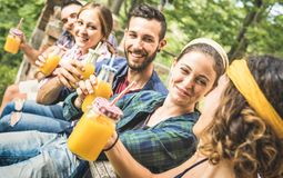 Happy Friends Drinking Healthy Orange Fruit Juice At Countryside Picnic - Young People Millennials Having Fun Together Outdoors Stock Photos