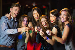 Happy friends drinking shots smiling at camera Royalty Free Stock Images