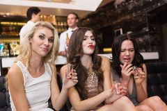 Happy friends drinking shots together Stock Images