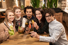 Happy friends with drinks at bar or cafe Stock Images