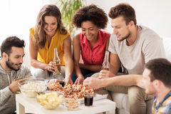 Happy friends with drinks eating pizza at home Stock Images