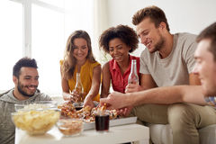 Happy friends with drinks eating pizza at home Royalty Free Stock Image