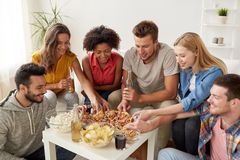 Happy friends with drinks eating pizza at home Stock Photos