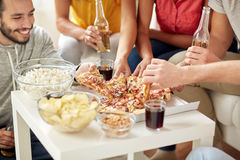 Happy friends with drinks eating pizza at home Royalty Free Stock Images