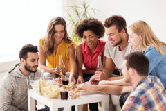 Happy friends with drinks eating pizza at home Royalty Free Stock Photography