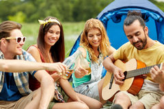 Happy friends with drinks and guitar at camping Stock Photography