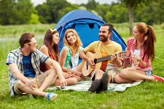 Happy friends with drinks and guitar at camping Royalty Free Stock Photos