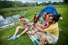 Happy friends with drinks and guitar at camping Royalty Free Stock Photo
